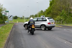 Motorcycle and car at a junction